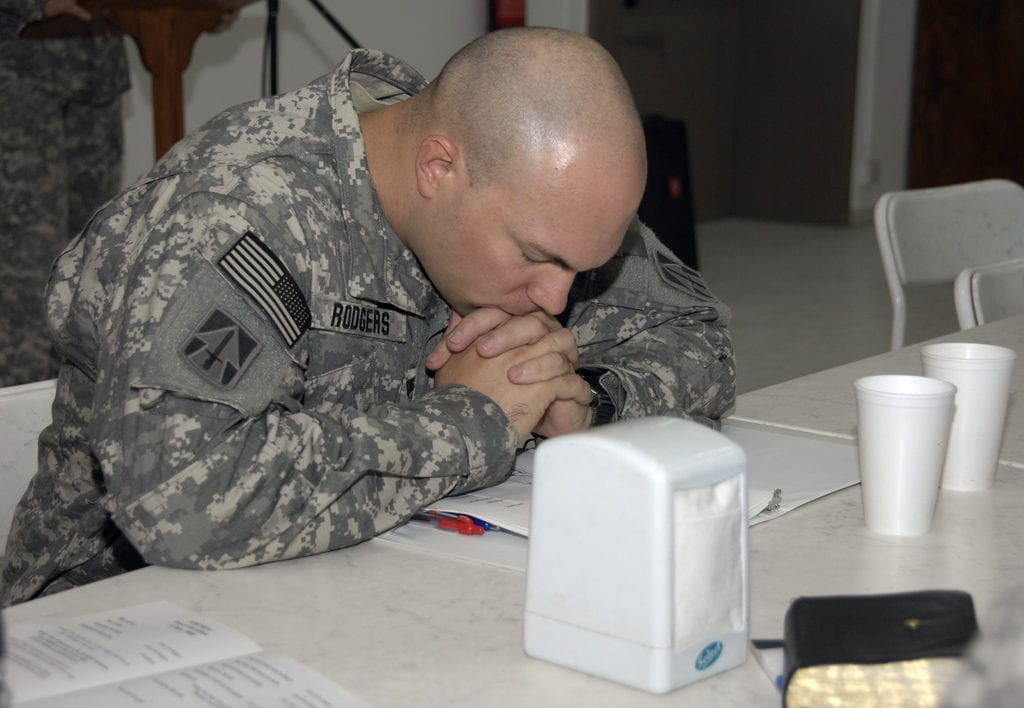 U.S. Army Capt. Adin Rodgers, a chaplain, bows his head in prayer at the dining facility, Forward Operating Base Marez, Mosul, Iraq, July 11, 2008, during a prayer breakfast. Rodgers is assigned to 1st Battalion, 163rd Field Artillery Regiment. (U.S. Army photo by Pfc. Sarah De Boise/Released)