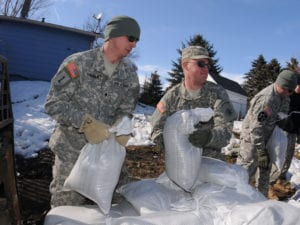 Spc. Tim Sybrant, of the 817th Engineer Sapper Company (Jamestown, N.D.), left, passes sandbags to Pfc. Scott Ness, of the 188th Engineer Company (Wahpeton, N.D.), March 17, in the Backyard of Konny Zinns and her husband Sgt. Darin Zins, who is currently deployed to Kosovo and can do little more than empathize with his family during Skype calls from half a World away. He serves with the 231st Maneuver Task Force, part of the NATO peacekeeping forces in Kosovo Force 12. The soldiers are building a sandbag flood barrier to hold back rising water from the Sheyenne River. (DoD photo by Senior Master Sgt. David H. Lipp) (Released)