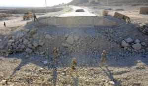 Military engineers from Provincial Reconstruction Team Zabul and the 2nd Stryker Calvary Regiment walk through the rubble of a bridge construction site on Highway 1 during a quality assurance, quality control visit on Nov. 14, 2010. PRT Zabul is comprised of Air Force, Army, Department of State, U.S. Agency for International Development and U.S. Department of Agriculture personnel who work with the government of Afghanistan to improve governance, stability, and development throughout the province. (U.S. Air Force photo by Staff Sgt. Brian Ferguson)