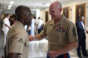 Sgt. Maj. of the Marine Corps Micheal P. Barret motivates Lance Cpl. Ethan Cadore during the unveiling of the Navy's tribute to African American leadership Mural. Cadore was one of six sentries standing guard for the ceremony. The mural honors African Americans who led the way in both the Navy and the Marine Corps.