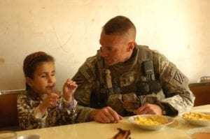 Noor, a young girl receiving eye surgery in the U.S., entertains 1st Lt. Michael Kendrick while he eats breakfast at her family's house in al-Buaytha, Iraq, May 25. Noor suffers from sclerocornea, a condition which has left her blind since birth. With help from Kendrick and other Soldiers of 1-30th Inf. Regt., she is traveling to the U.S. for surgery that may restore her vision. Photo by Sgt. David Turner<br /> see http://www.army.mil/-news/2008/05/27/9433-iraqi-girl-travels-to-us-in-effort-to-repair-vision/