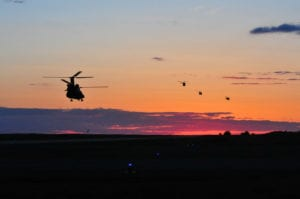 Three UH-60 Blackhawks from the Maryland National Guard's 224th Aviation Regiment leave on a mission to insert troops into battle with a CH-147F Chinook from the Royal Canadian Air Force's 450 Tactical Helicopter Squadron at Camp Wainwright, Alberta, Canada, on May 26, 2017. The 224th is supporting Maple Resolve 17, the Canadian Army's premier brigade-level validation exercise designed to sharpen individual skill sets and enhance unit readiness running 14-29 May.
