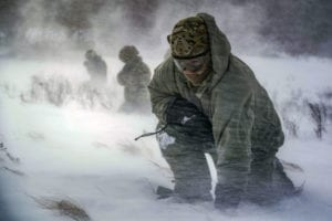 Staff Sgt. Benjamin Reynolds, 891st Missile Security Forces Squadron response force leader, crouches in rotor wash during a field training exercise at Turtle Mountain State Forest, N.D., Feb. 14, 2018. During the exercise, 91st Security Forces Group defenders coordinated simulated medical evacuations with two 54th Helicopter Squadron UH-1N Iroquois. (U.S. Air Force photo by Senior Airman J.T. Armstrong)