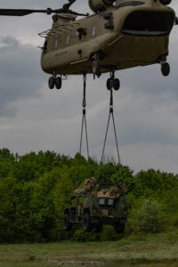 An Army Ground Mobility Vehicle (AGMV) is lowered to the ground by a CH-47 Chinook helicopter during exercise Immediate Response 19 at Military Training Area Eugen Kvaternik, Croatia, May 18, 2019. This is the first operational use of the new vehicle, designed to be more agile and mobile than other types of vehicles commonly used by the U.S. Military. (U.S. Army photo by Pvt. Laurie Ellen Schubert, 5th Mobile Public Affairs Detachment)