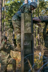 While competing for the Expert Field Medical Badge, a Soldier scales a roughly 7-foot wall in order to successfully get a simulated casualty to safety on Nov.r 3, 2018, at Fort Bragg, N.C. The first week of testing introduces the candidates to all the tasks that they'll be expected to complete to earn the coveted badge. The EFMB was established to showcase and recognize medical Soldiers for their exceptional skill level and competence in the medical field. The testing consists of a written exam, land navigation, three separate combat testing lanes and concludes with a 12-mile ruck march. (U.S. Army photo by Sgt. Dustin Biven / 22nd Mobile Public Affairs Detachment)