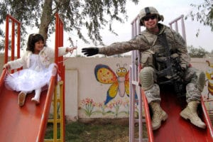 Sgt. Stephen Covell, a native of Pacific Grove, Calif., along with an Iraqi girl go down a slide at the playground during the reopening of the Al-Moutasam Kindergarten March 3 in the Rusafa district of eastern Baghdad. Covell is a medic assigned to Headquarters and Headquarters Troop, 5th Squadron, 73rd Cavalry Regiment, 3rd Brigade Combat Team, 82nd Airborne Division, Multi-National Division-Baghdad