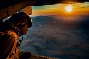 """Sgt. Derek Levi, MV22 crew chief, Marine Medium Tilt Rotor Squadron, Marine Aircraft Group 16, 3rd Marine Aircraft Wing looks over the landscape of Marine Corps Air Ground Combat Center, Twentynine Palms, Calif., during an aerial flight formation exercise August 12, 2018. """"I get to see the world from the sky,"""" said Sgt. Derek Levi, MV22 crew chief, Marine Medium Tilt Rotor Squadron, Marine Aircraft Group 16, 3rd Marine Aircraft Wing, """"While I work on the ground, I get to work on the aircraft while watching young Marines become experts in their field and leaders of others."""" The exercise was completed as a form of demonstration of the capabilities of the VMM-165. (U.S. Marine Corps photo by Lance Cpl. Rachel K. Young)"""