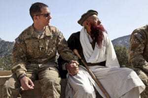 KUNAR PROVINCE, Afghanistan – U.S. Army Capt. Mark Moretti, commander of Company B, 2nd Battalion, 12th Infantry Regiment, Task Force Lethal Warrior, sits hand-in-hand with Shamshir Khan, one of the most senior Korengal Valley elders, April 13, at the Korengal Outpost in Kunar province, Afghanistan. Moretti, who has led the Soldiers of Baker Company at the KOP since 2009, welcomed Khan and the rest of the Korengali elders onto the KOP to provide them an orientation of all the buildings and equipment that would be left behind for the people of the valley to utilize. International Security Assistance Forces and Afghan National Security Forces completed the repositioning of forces out of the Korengal Valley into more populated areas in accordance with the ISAF counterinsurgency strategy early April 14, 2010. (Photo by U.S. Army Spc. David Jackson, 55th Signal Company)