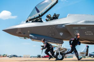 F-35 Lightning II demonstration team members sprint to their positions during the ground show at the Defenders of Liberty Air & Space Show at Barksdale Air Force Base, La., May 17, 2019. The team's ground show consists of pre-flight inspections with sharp, quick-paced movements that showcase the pride and professionalism of the U.S. Air Force. (U.S. Air Force photo by Senior Airman Alexander Cook)