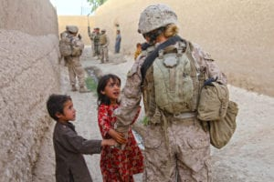 "Lance Cpl. Chandra Francisco, with Female Engagement Team 15 in Sangin District, Helmand province, holds hands and talks with Afghan children during a patrol, July 17. Chandra, of Monroe, Wash., was put on FET by her parent unit, II Marine Expeditionary Force Headquarters Group, last fall, and says, ""At first I really had no idea what I was getting into. Once I started training I loved it. This is by far one of the greatest experiences I've ever gotten to have."""