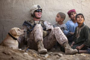 """U.S. Marine Lance Cpl. Isaiah Schult, a 20-year-old Indianapolis native and improvised explosive device dog handler with Jump Platoon, Headquarters and Service Company, 3rd Battalion, 3rd Marine Regiment, jokes with Afghan children and a Afghan National Police member outside a local residence here, Nov. 22. Following their recent assumption of security responsibility in Garmsir, the leadership of """"America's Battalion"""" joined District Governor Mohammad Fahim to visit and interact with citizens throughout the district, Nov. 22 to 24. During the visits, Fahim and the Marines discussed issues like tribal unity, education, insurgent activity and the continued development of the Afghan National Army and Police. """"We're bringing governance to ungoverned places,"""" said Lt. Col. Matthew Palma, 3/3 commanding officer. """"Now, it's up to the Afghan people to work together with their government to make the changes required to become free."""""""